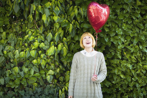 Smiling young woman holding heart shape balloon while standing against plants - FSIF03154