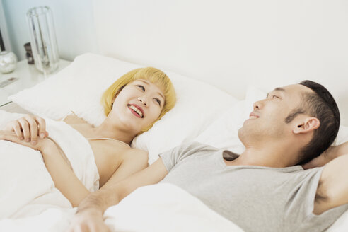 Smiling young couple lying on bed at home - FSIF03157