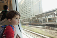 Curious boy looking through glass window while traveling in train - FSIF03160