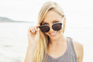 Portrait of woman wearing sunglasses looking at camera smiling - ISF09262