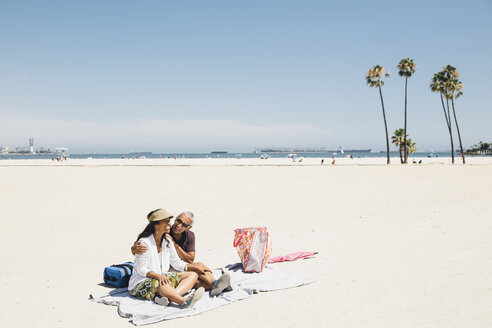 Senior couple sitting on picnic blanket on beach, Long Beach, California, USA - ISF09328
