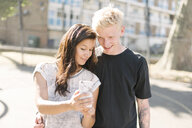 Woman and boyfriend reading smartphone update on basketball court - CUF23188
