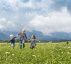 Grandmother and grandchildren running in field holding hands, Fuessen, Bavaria, Germany - CUF23248