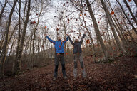 Hikers throwing leaves in woods, Montseny, Barcelona, Catalonia, Spain - CUF23296