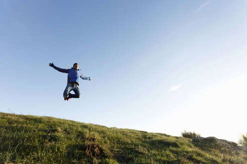 Hiker jumping on hilltop, Montseny, Barcelona, Catalonia, Spain - CUF23299