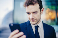 Businessman texting on smartphone in front of office - CUF23317