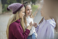Smiling teenage girls making a pinky promise - ZEF15603
