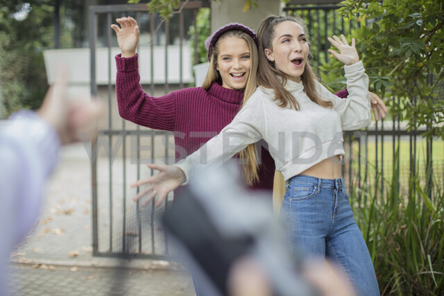 Teenage girl taking a picture of her happy friends outdoors - ZEF15606