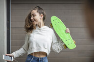 Carefree teenage girl dancing while holding skateboard and listening to music - ZEF15612
