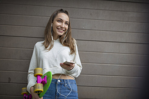 Smiling teenage girl with cell phone, earphones and skateboard - ZEF15615
