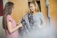 Two smiling teenage girls choosing clothes from wardrobe - ZEF15633