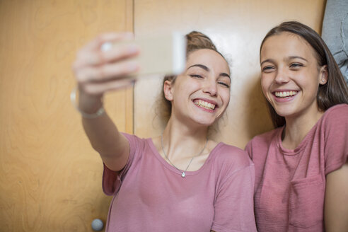 Portrait of two happy teenage girls taking a selfie - ZEF15639