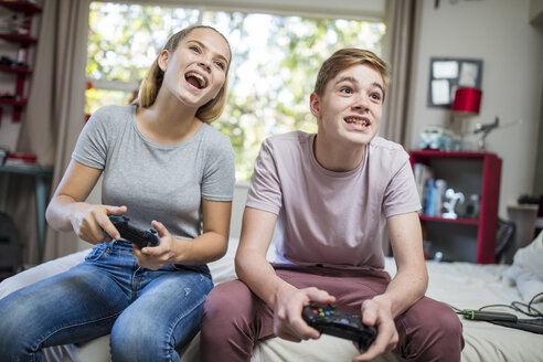 Happy teenage girl and boy sitting on bed playing video game - ZEF15642