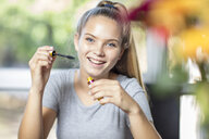 Portrait of smiling teenage girl applying makeup - ZEF15648