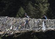 Nepal, Solo Khumbu, Everest, Sagamartha National Park, Two people crossing suspension bridge - ALRF01247