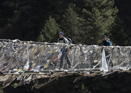 Nepal, Solo Khumbu, Everest, Sagamartha National Park, Two people crossing suspension bridge - ALRF01247