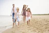 Family running along sandy beach - CUF23436