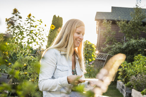 Woman looking at laptop in community garden, Vancouver, Canada - CUF23451