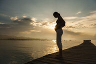 Silhouette of pregnant woman standing on pier, Majorca, Spain - CUF23472