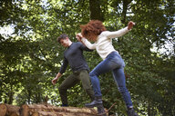 Couple in forest holding hands balancing on fallen tree - CUF23487