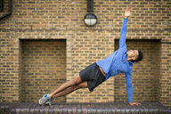 Man stretching in front of brick wall, Wapping, London, UK - CUF23520