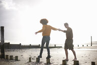 Man helping woman balance on wooden stumps on beach - CUF23538
