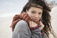 Portrait of young woman wrapped in scarf on windy beach, Western Cape, South Africa - CUF23583