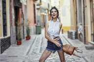 Portrait of fashionable woman with small backpack in the city - JSMF00297