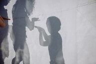 Family doing a shadow play behind sail - JLOF00010