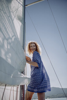 Smiling woman standing on a sailing boat - JLOF00052