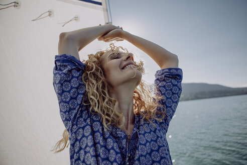 Carefree woman on a sailing boat in backlight - JLOF00058