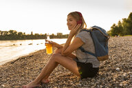 Blond woman with earphone and bottle sitting on riverside in the evening, listening music - UUF14046