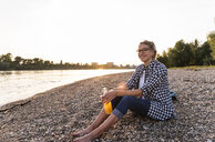 Blond woman sitting on riverside in the evening - UUF14058