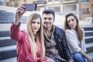Young woman taking smartphone selfie with friends on stairway, Cagliari, Sardinia, Italy - CUF23698