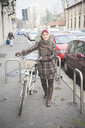 Portrait of young woman walking down street with bicycle, wearing winter clothes - CUF23731