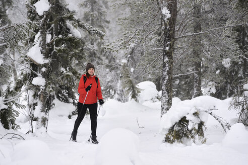 Young woman nordic walking through snow covered forest, Posio, Lapland, Finland - CUF23734