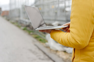 Man holding laptop, construction site in the background - KNSF03978