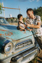 USA, Arizona, Father and baby playing with a reproduction of an old vintage car, at Route 66 - GEMF02060