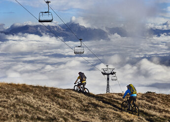 Two mountain bikers under cable cars, Valais, Switzerland - CUF23888