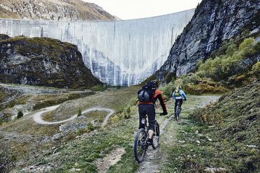 Mountain bikers by dam, Valais, Switzerland - CUF23915