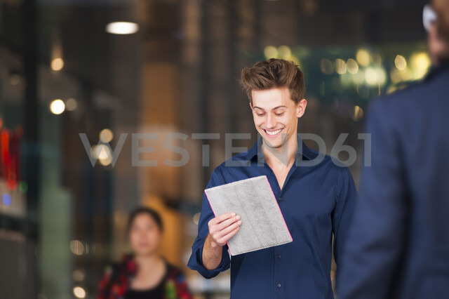 Young man strolling in shopping mall reading digital tablet - CUF23933 - Daniel Ingold/Westend61