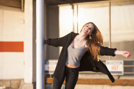 Smiling young woman swinging on pole in parking lot - CUF23942