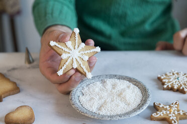 Man's hand holding homemade Christmas Cookie, close-up - SKCF00488