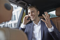 Young businessman in taxi back seat chatting on smartphone - CUF24026