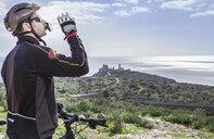 Mid adult male mountain biker drinking water on coastal path, Cagliari, Sardinia, Italy - CUF24038
