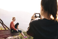 Over shoulder view of young woman photographing friend at Lake Atitlan, Guatemala - CUF24071