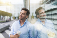 Portrait of mature businessman drinking takeaway coffee and gazing - CUF24086