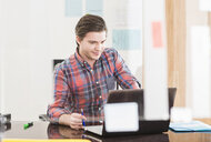 Young businessman looking at laptop on office desk - CUF24266