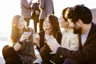Group of friends laughing and drinking at party - CUF24311