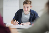 Smiling teenage boy taking notes in class - ZEF15668